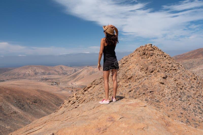 Расслабленная девушка смотря ландшафт от вершины горы стоковые изображения