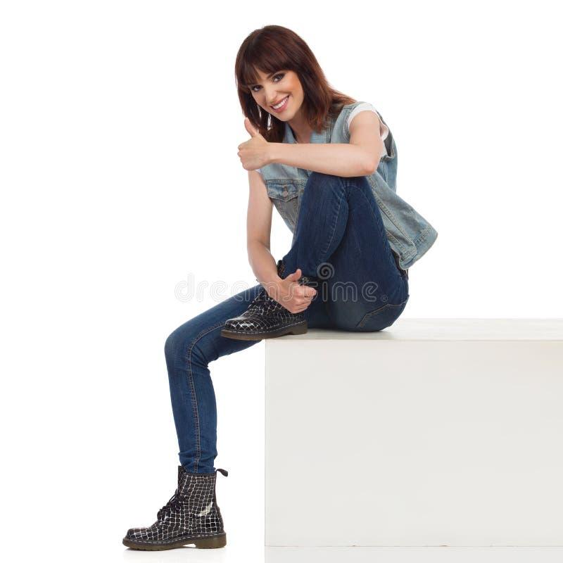 Расслабленная девушка утеса сидит на белой коробке, показывает большой палец руки вверх, усмехается и смотрится камеру стоковые фото