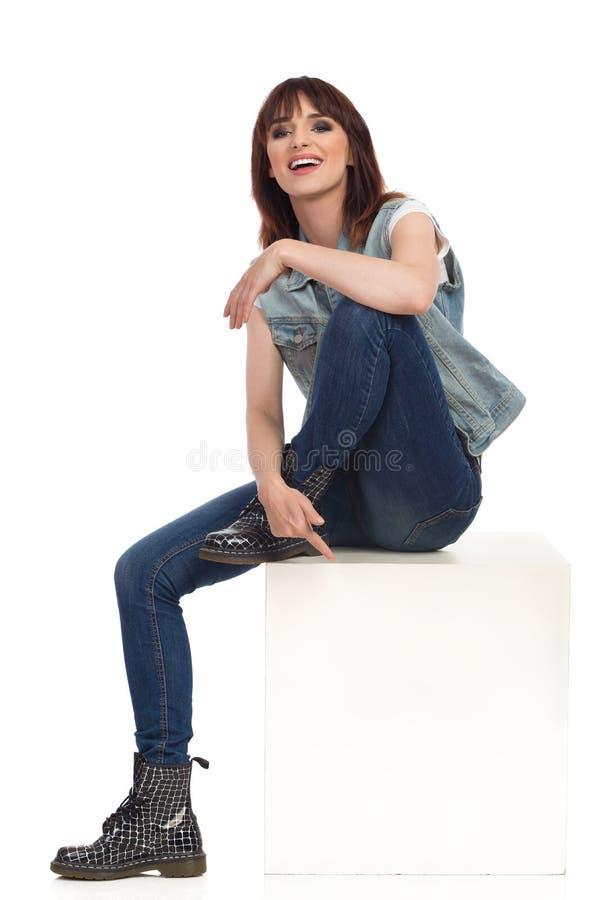 Расслабленная девушка утеса сидит на белой коробке, усмехается и смотрится камеру стоковые фотографии rf