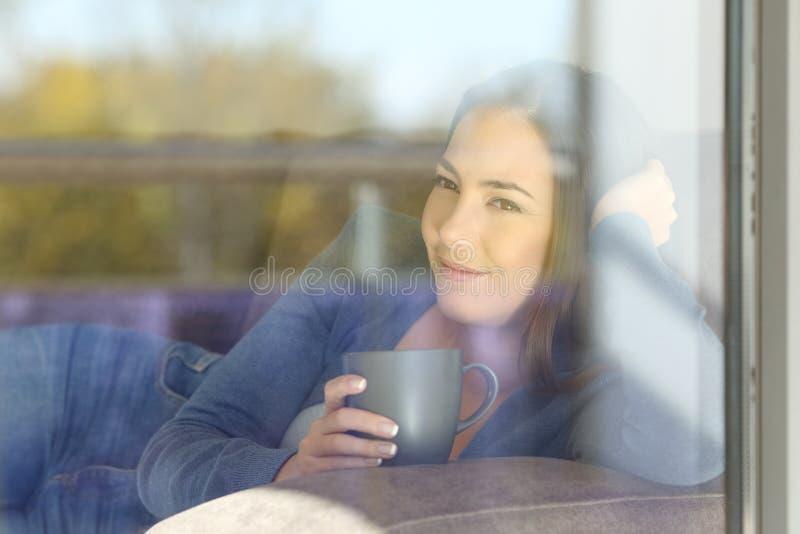 Расслабленная женщина смотря outdoors через окно стоковая фотография