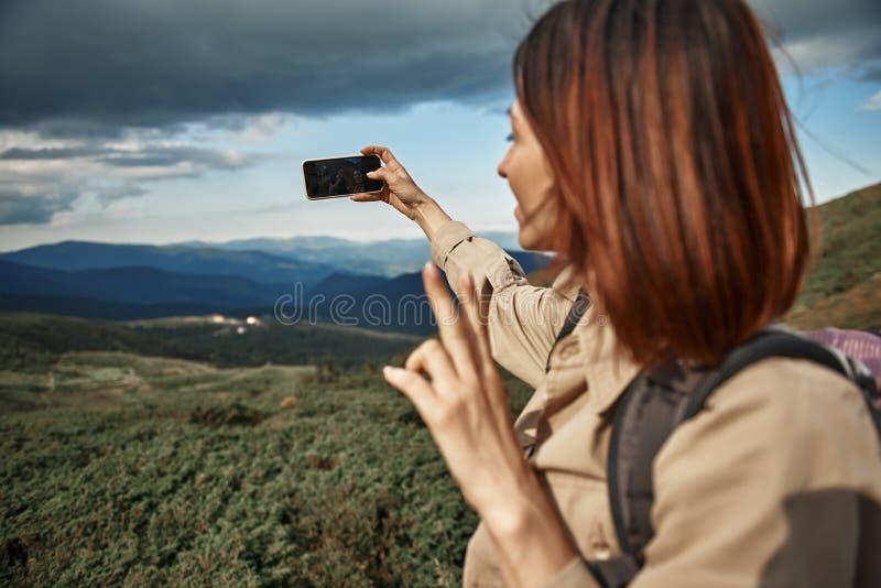Расслабленная женщина усмехаясь к камере и принимая selfies стоковое изображение rf