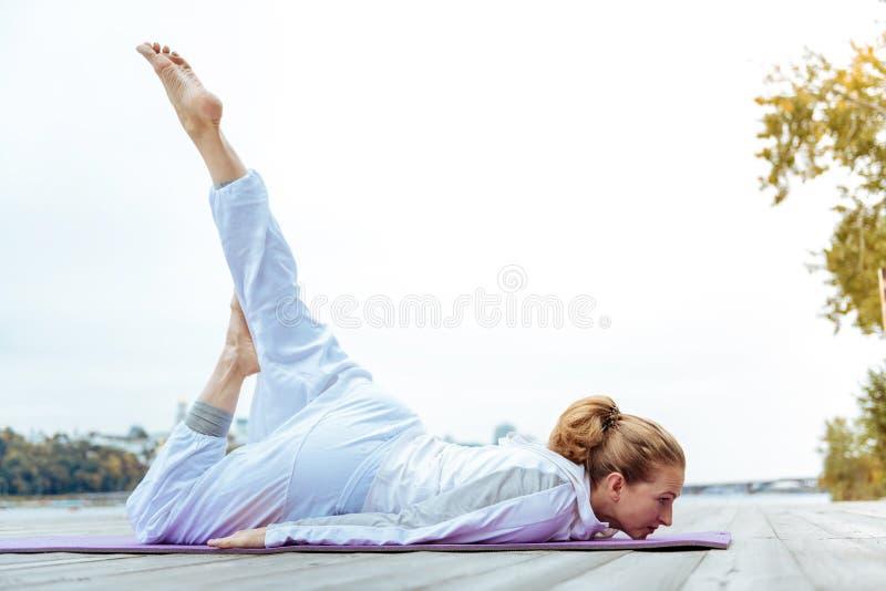 Расслабленная молодая женщина легко практикуя представления йоги стоковое фото