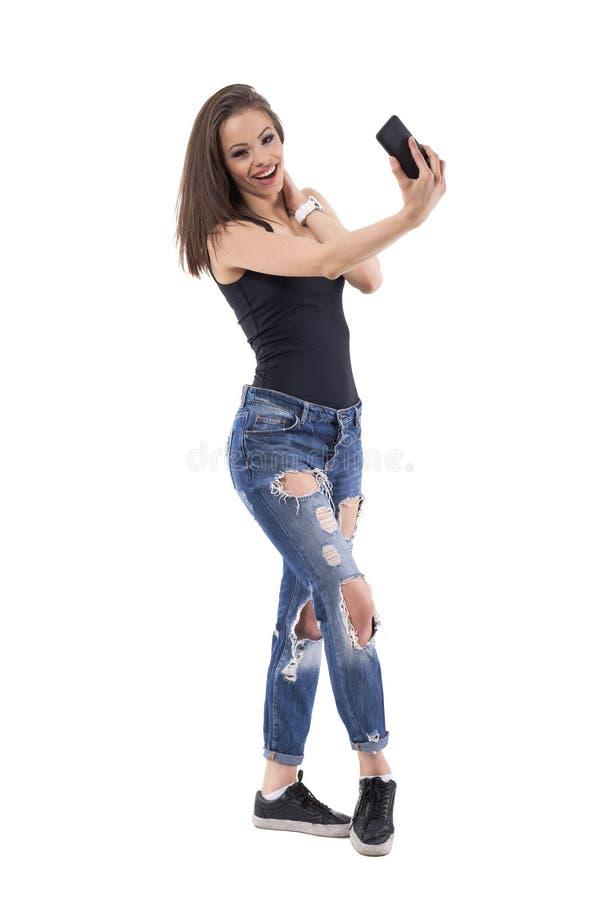 Расслабленная молодая красивая счастливая женщина имея потеху с камерой мобильного телефона стоковая фотография rf