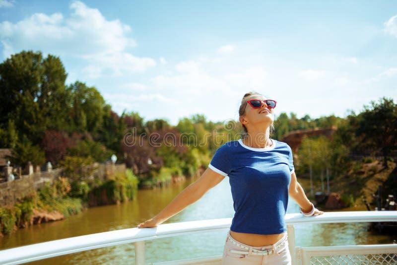 Расслабленная подходящая женщина на лодке наслаждаясь курсировать реки стоковая фотография rf