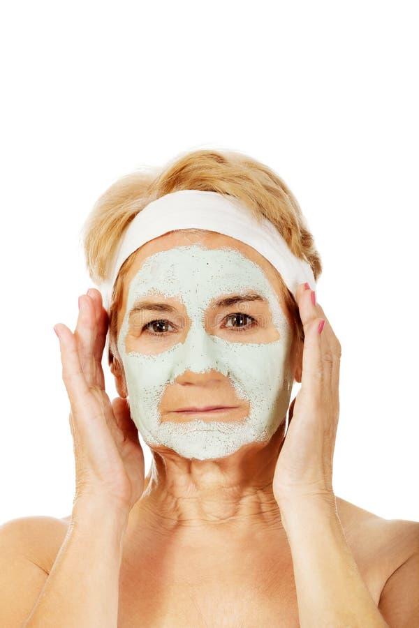 Расслабленная пожилая женщина в лицевой маске стоковые изображения rf