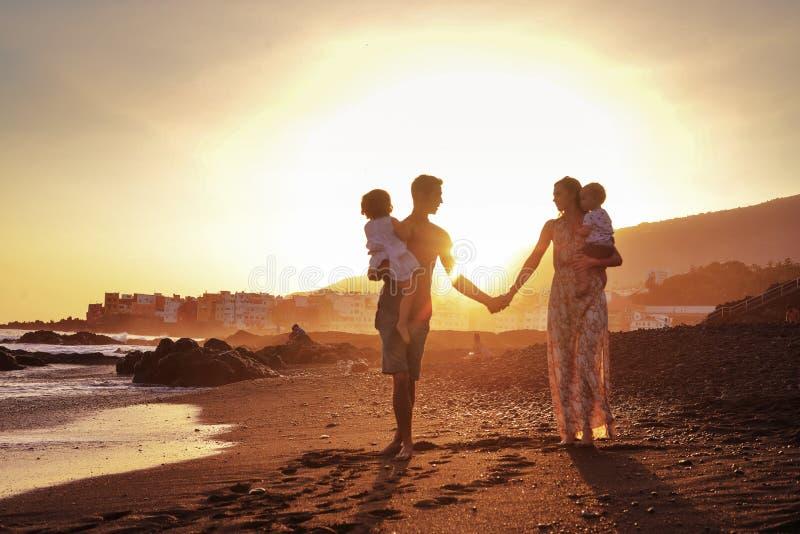 Расслабленная семья на тропическом пляже, красивом заходе солнца стоковые фото