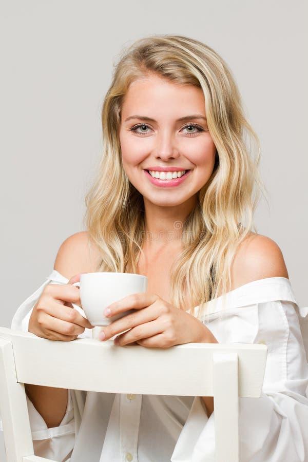Расслабленное белокурое имеющ кофе стоковое фото
