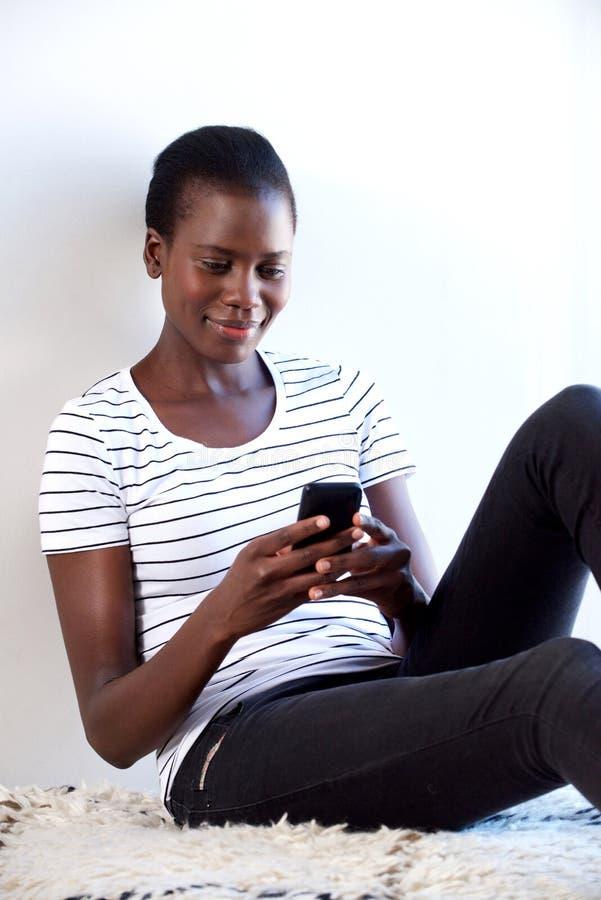 Расслабленное молодое африканское текстовое сообщение чтения женщины на мобильном телефоне стоковое фото