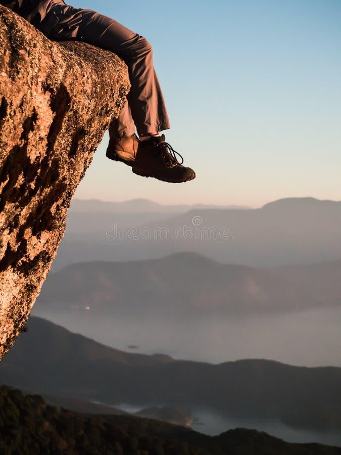 Расслабленные ноги на верхней части горы на заходе солнца стоковое изображение