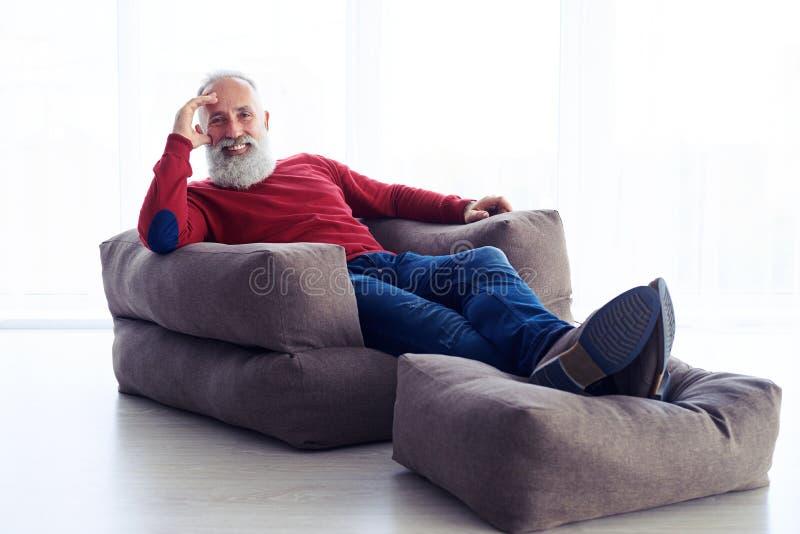 Расслабленный бородатый человек сидя в кресле рядом с окном на ho стоковые изображения