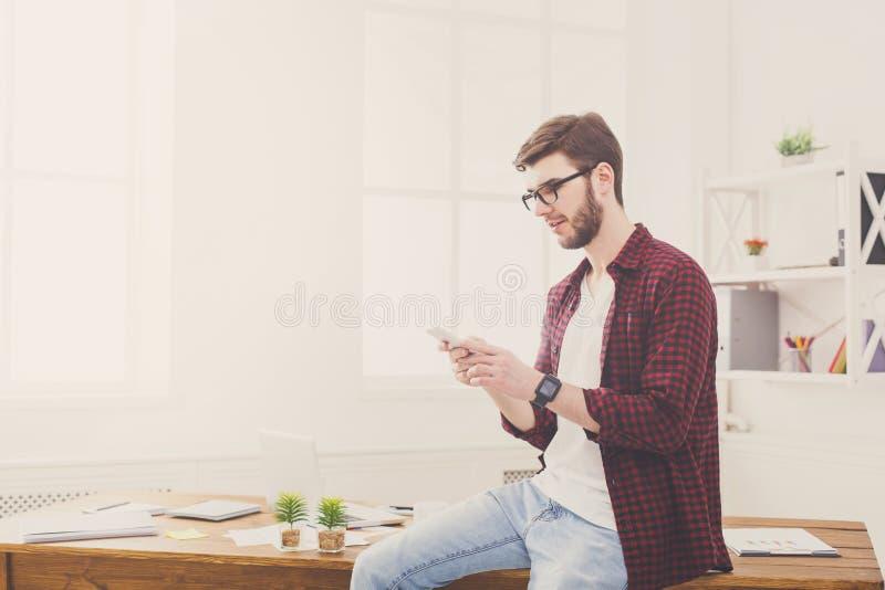 Расслабленный молодой бизнесмен используя чернь в офисе стоковые изображения
