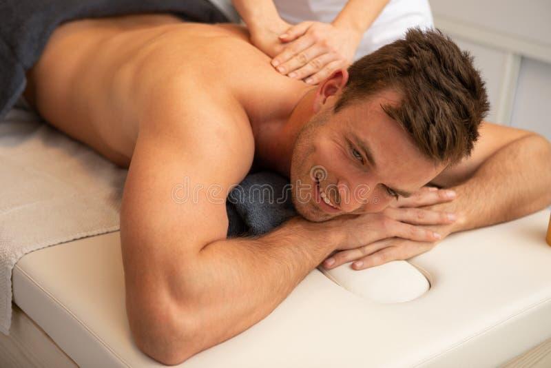 Расслабленный молодой человек получая задний массаж стоковые фото
