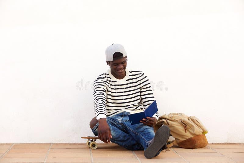 Расслабленный молодой человек сидя на скейтборде outdoors и книге чтения стоковое фото