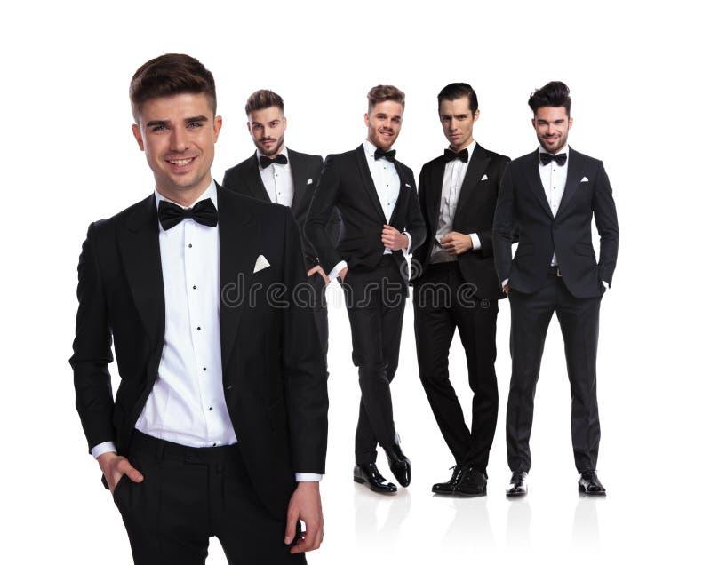 Расслабленный руководитель группы groomsmen стоит в фронте и улыбках стоковое фото rf