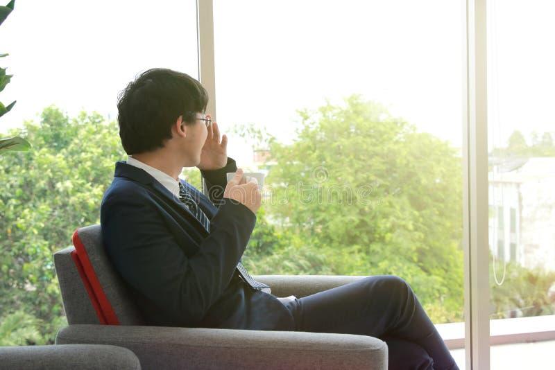 Расслабленный элегантный азиатский бизнесмен держа кофейную чашку в офисе Концепция торжества успеха стоковая фотография rf
