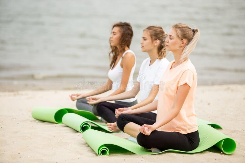 3 расслабленных маленькой девочки сидят в положениях лотоса с глазами заключения делая йогу на циновках на песчаном пляже на тепл стоковое изображение