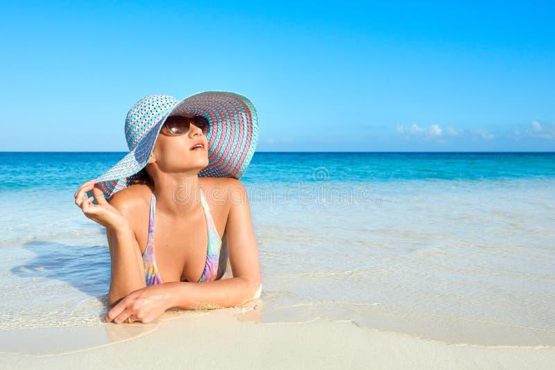 Расслабляющая женщина в бикини и шляпе лета наслаждаясь солнцем лета стоковая фотография rf