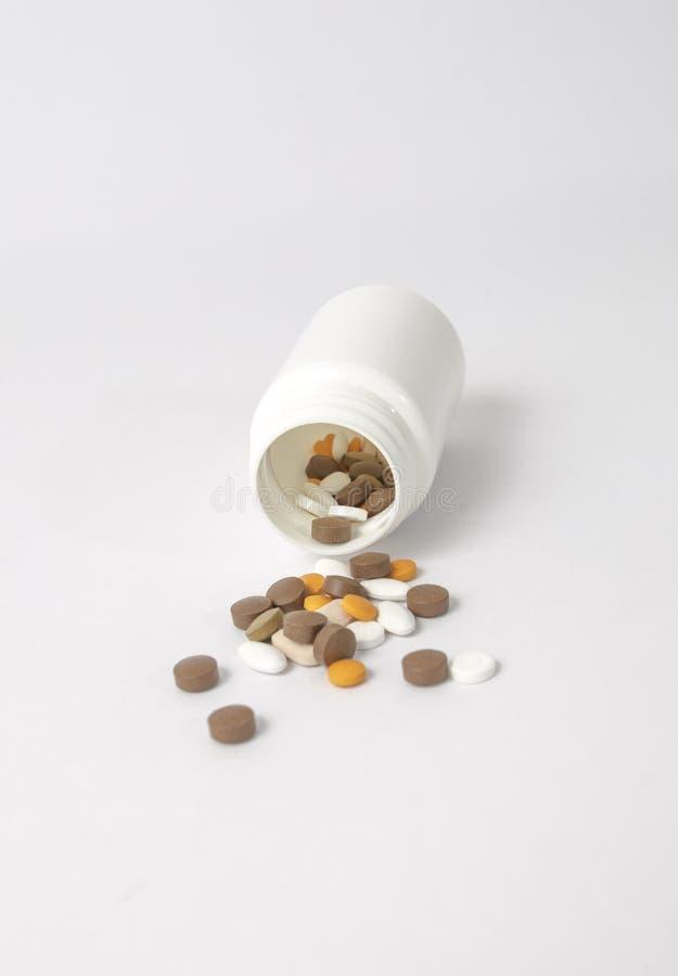 расслоина таблеток от белой бутылки лекарства стоковые изображения rf