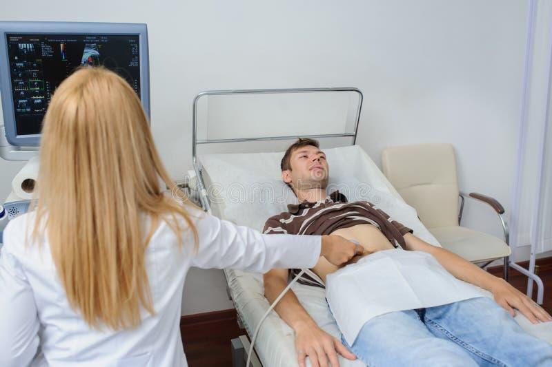 Рассмотрение доктора человек на брюшке Usg стоковая фотография