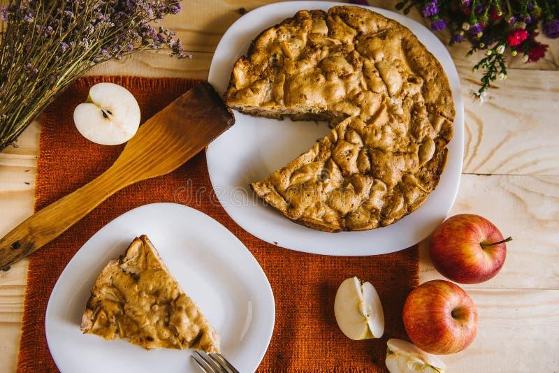 расстегай яблока домодельный Состав осени с пирогом, яблоками, цветками Плоская предпосылка еды положения стоковые фото