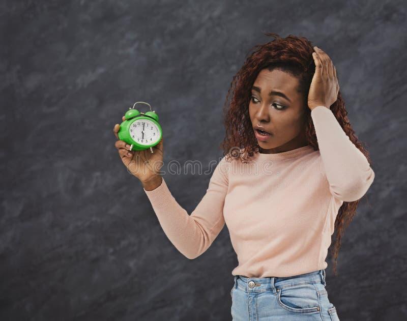 Расстроенная Афро-американская женщина смотрит будильник стоковые изображения
