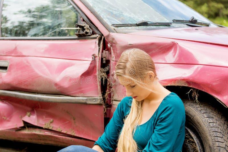 Расстроенная женщина водителя перед автомобилем аварии автомобиля стоковая фотография rf
