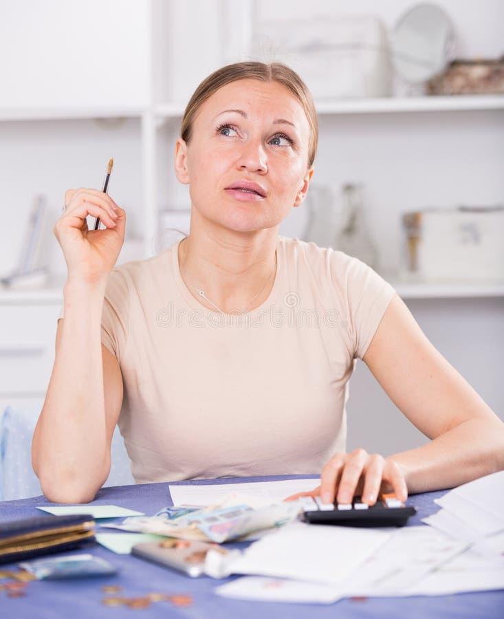 Расстроенная женщина высчитывая финансы стоковые изображения