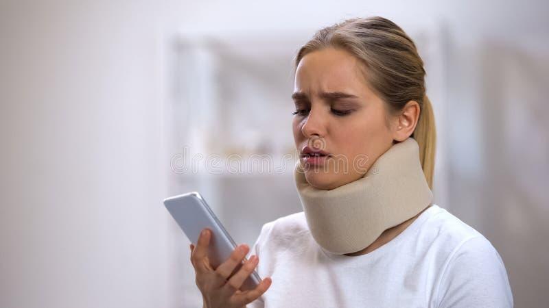 Расстроенная женщина в воротнике пены цервикальном смотря смартфон, полученную плохую новость стоковая фотография rf