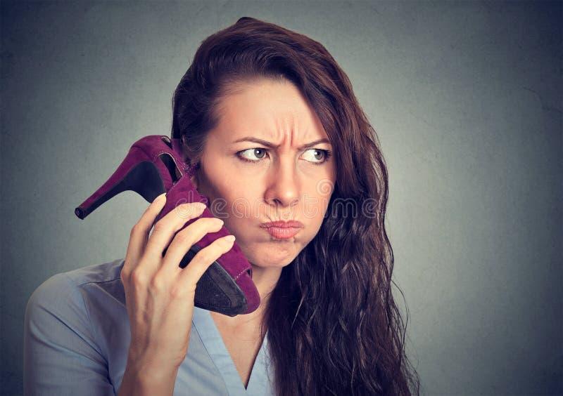 Расстроенная женщина держа максимум накренила ботинок в ее руке как телефон стоковые фотографии rf