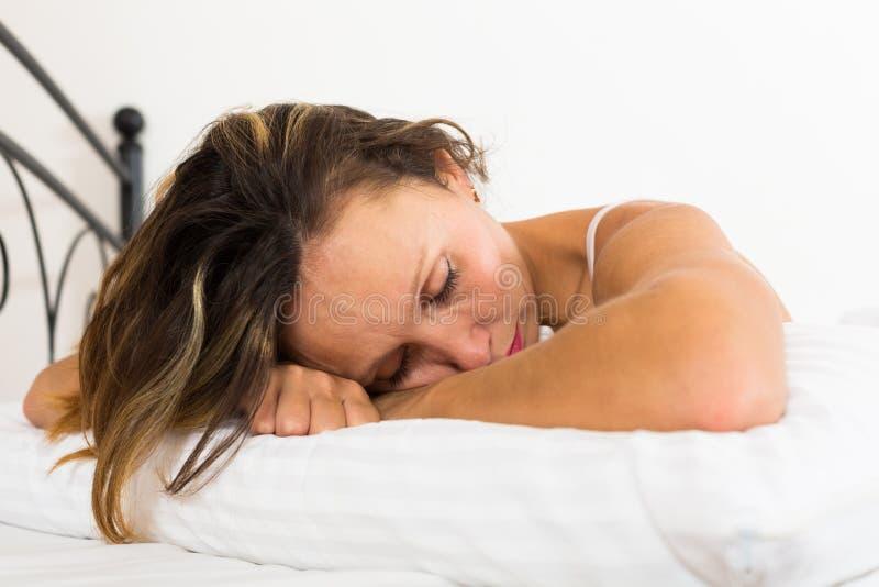 Расстроенная женщина кладя в кровать стоковые изображения