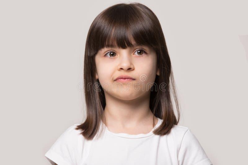 Расстроенная маленькая девочка изолированная на серой предпосылке студии стоковое изображение