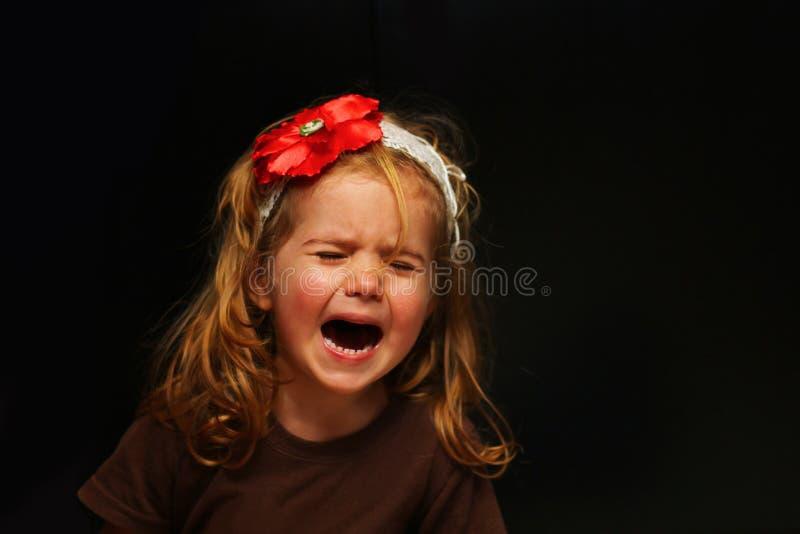 Расстроенная маленькая девочка плача вне нагрузка, портрет изолированный на черноте стоковое изображение