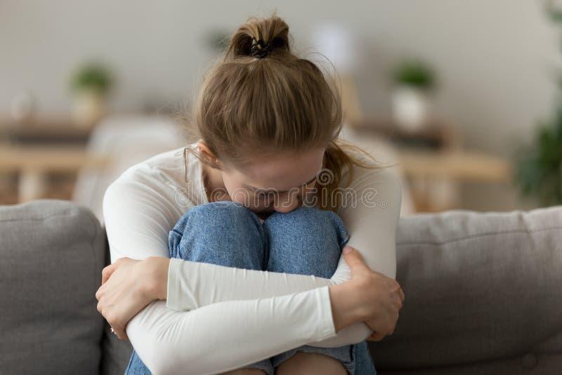 Расстроенная разочарованная женщина сидя на кресле, обнимает колени,  стоковые изображения rf