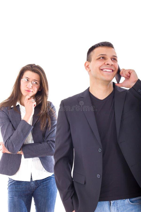 Расстроенная ревнивая женщина смотря ее человека беседуя на телефоне стоковые фотографии rf