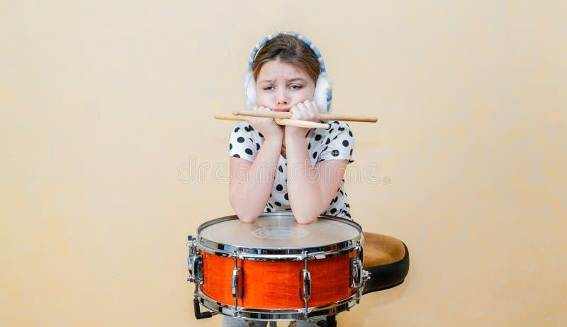Расстроенное сверлильное усаживание маленькой девочки, думая за барабанчиком тенет стоковые фото