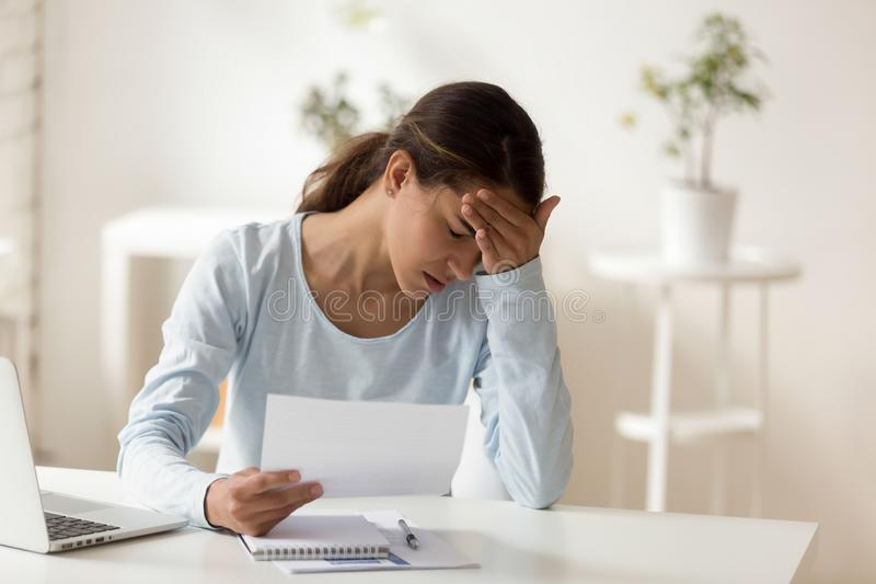 Расстроенное усиленное уведомление чтения женщины, получать плохой новости стоковая фотография