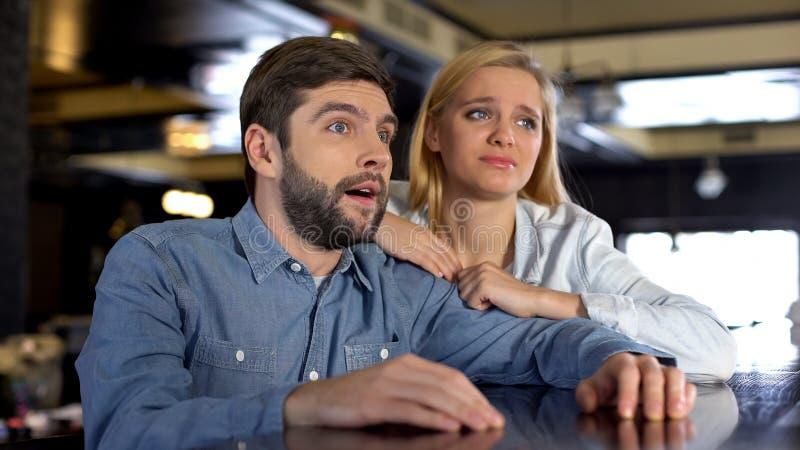 Расстроенные болельщики пар наблюдая игру совместно, плохой результат спички, разочарование стоковое фото rf