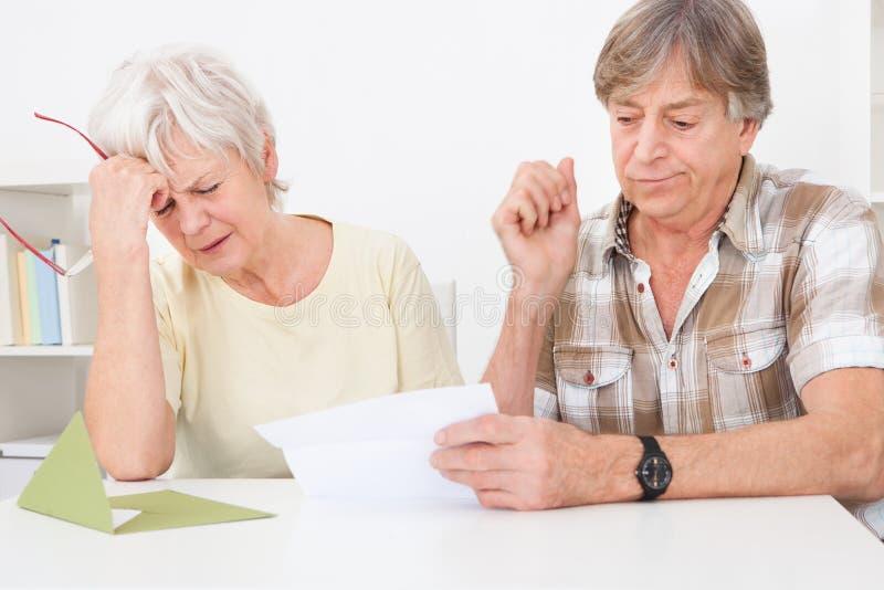 Расстроенные старшие пары с письмом стоковое изображение