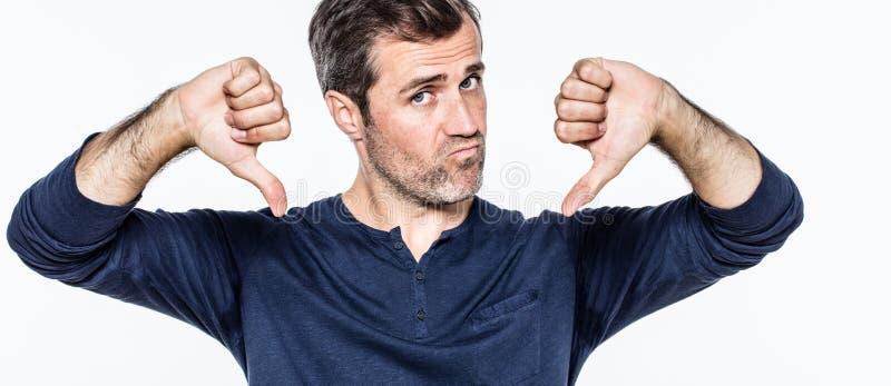 Расстроенный красивый молодой бородатый человек показывая отрицательные большие пальцы руки вниз стоковые изображения