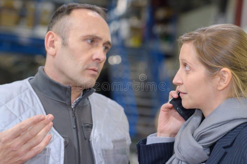 Расстроенный мужской работник говоря к женскому коллеге в складе стоковые фото