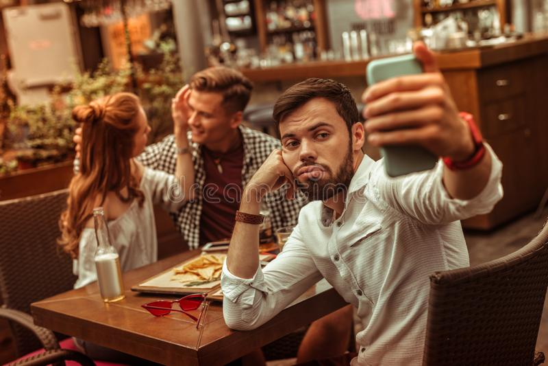 Расстроенный мужчина принимая selfies пока его ответные части прижимаясь на предпосылке стоковое фото