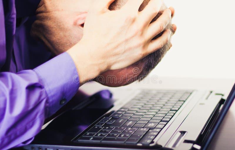 Расстроенный разочарованный бизнесмен перед портативным компьютером стоковое изображение