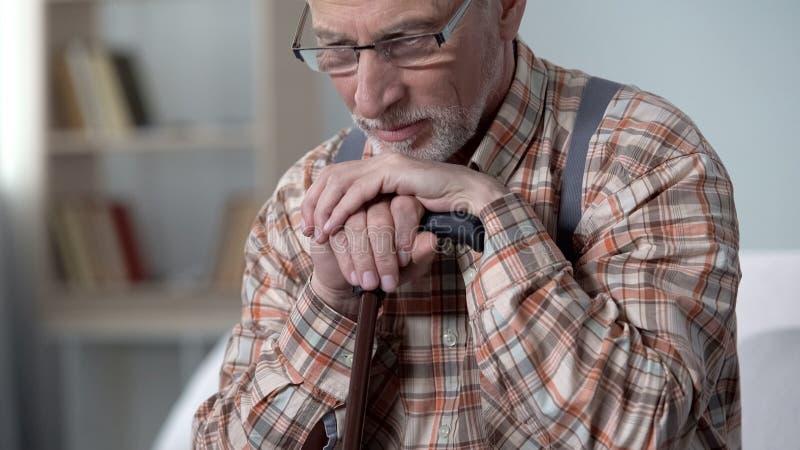 Расстроенный старик полагаясь на идя ручке, чувствует сиротливым, вспоминающ молодость, крупный план стоковые фотографии rf