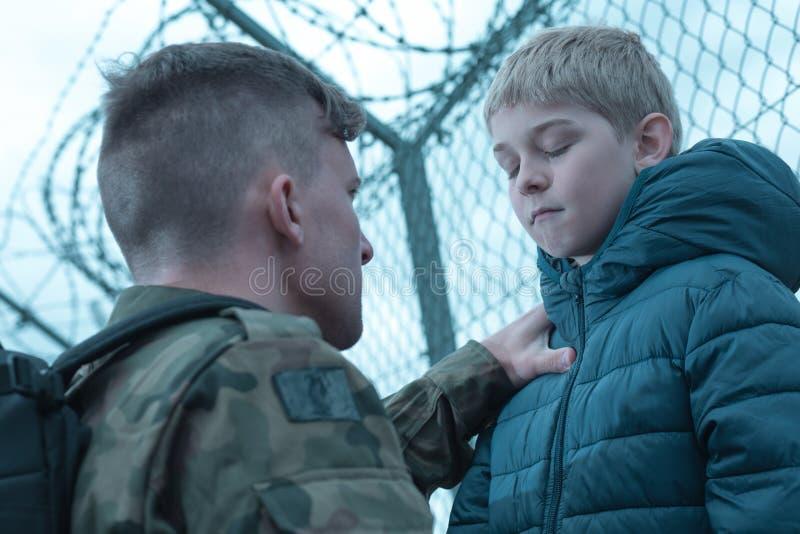 Расстроенный сын и воинский папа стоковая фотография