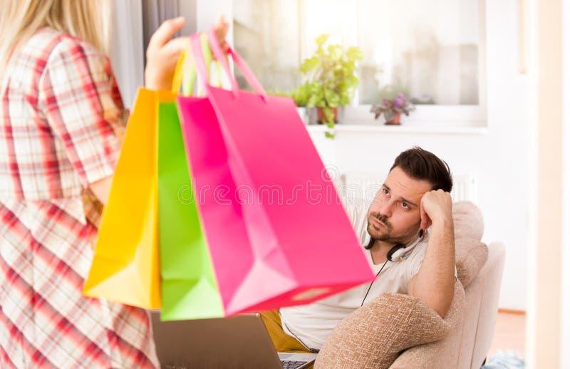 Расстроенный человек из-за покупок ` s девушки стоковое изображение