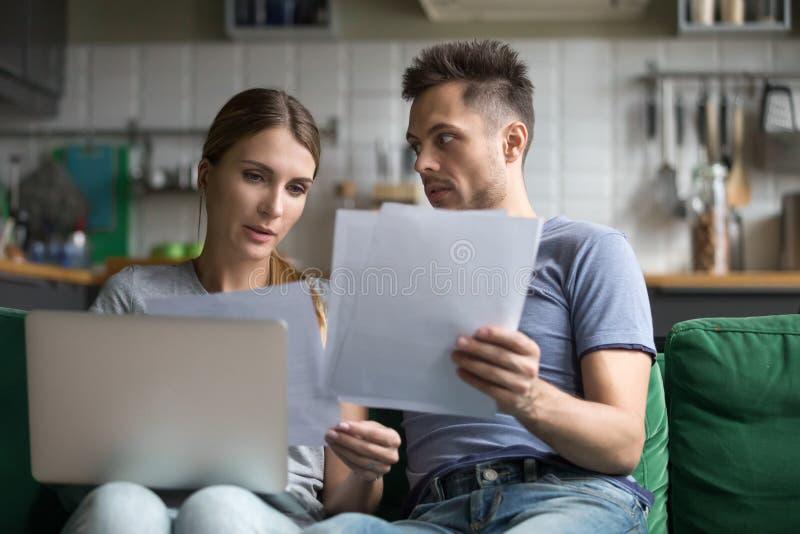Расстроенный человек и женщина используя ноутбук, документы проверки стоковое фото