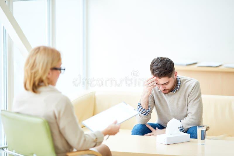 Расстроенный человек на посещении к психиатру стоковое изображение rf
