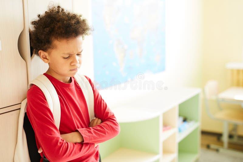 Расстроенный школьник на шкафчиках стоковое фото rf