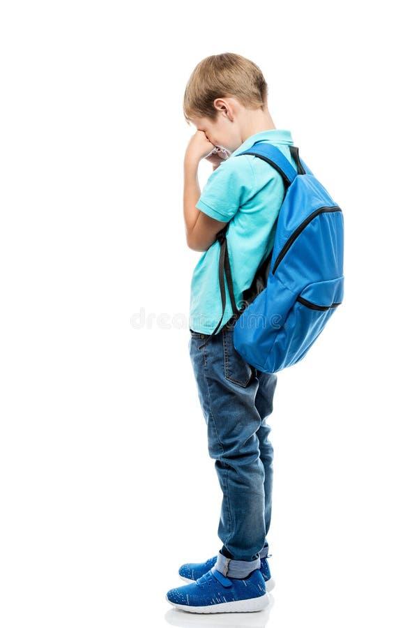 Расстроенный школьник с рюкзаком плача на белой предпосылке стоковые изображения