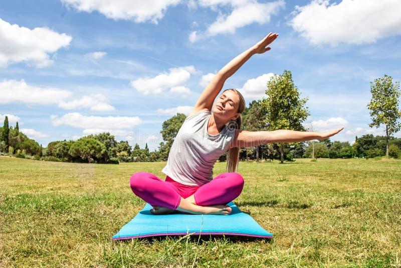 Расслабленная белокурая женщина делая йогу с изогнутым верхним телом стоковое фото rf
